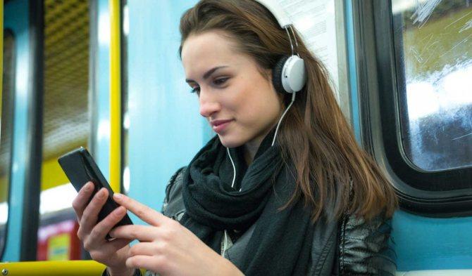 Девушка в наушниках в транспорте.